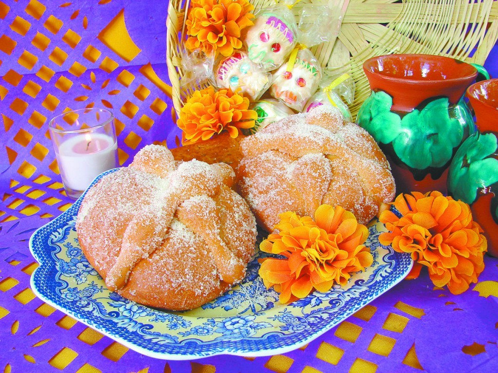 Bread of the dead and sugar skulls surrounded by orange marigolds